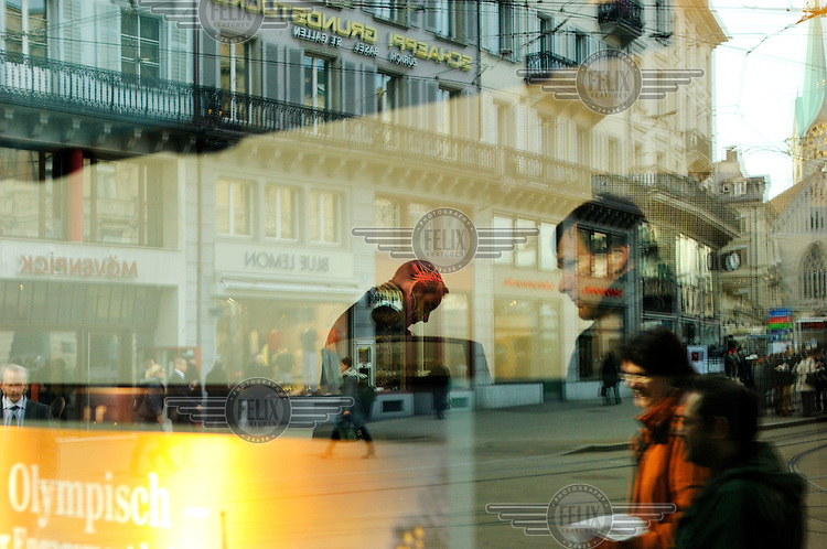 People inside the headquarters of UBS, Switzerland's largest bank, with Paradeplatz, the symbolic centre of the Swiss banking industry, reflected in the window. The Swiss banking industry holds an estimated 4,000 billion Swiss Francs (USD 4,240 billion) in assets, more than half of it foreign, including CHF 880 billion in undeclared European assets alone, benefiting from the country's famous banking secrecy laws.