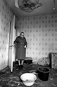 Bridie Walsh, a tenant on Westminster Council's Walterton Estate for twenty years, collects water from a leaking roof which has made her bedroom uninhabitable.