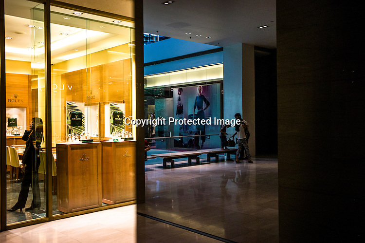 A shop attendant is seen inside the luxury watch store while the shoppers are reflected on the polished marble pillar at the Pavilion, a high end shopping mall in Kuala Lumpur, Malaysia.