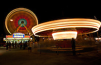 Carnival Scene of the carnival midway and ferris wheel and Merry-Go-Round spinning in austin, texas