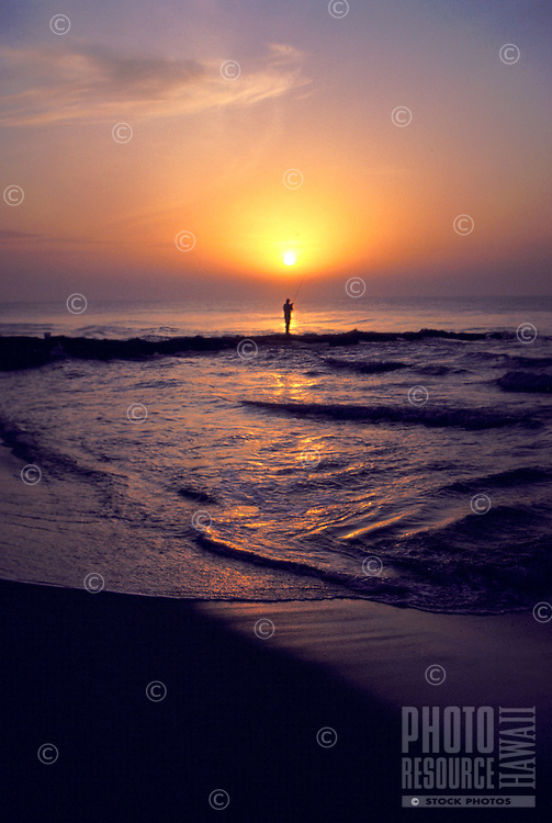 Man shoreline fishing at sunset, island of Kauai