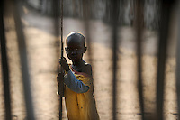 SOUTH-SUDAN Lakes state, Rumbek, Dinka child looking through fence / SUED-SUDAN Rumbek, Dinka Kind schaut durch einen Zaun