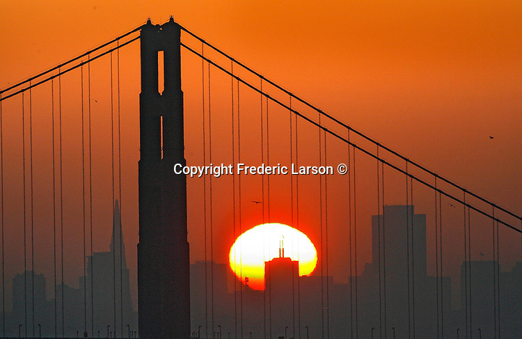 """""""Here comes the sun,"""" through the Golden Gate Bridge between the tallest buildings from Point Bonita the sunrise pokes through the low lying haze blanketing the city skyline."""