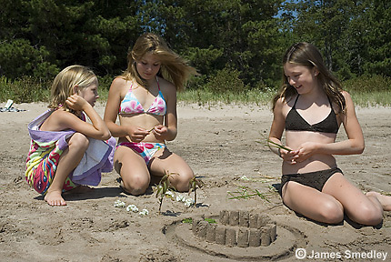 Three young girls building sand castles at the beach