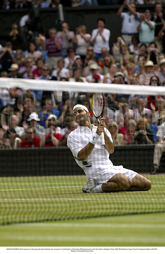 ROGER FEDERER (SUI) kneels on the ground and clutches his racquet in celebration of beating Philippoussis to win the Men's Singles Final, 2003 Wimbledon Lawn Tennis Championships, 030706. Photo: Glyn Kirk/Action Plus AP1099099...2003 player players men man .celebrate celebrating celebration celebrates joy.win wins winner winning