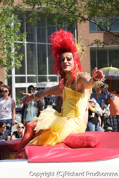 Mado Lamothe rides in a white Caddilac in the Pride Parade in Montreal