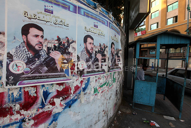 A Palestinian traffic policeman sits next to a picture for the leader in Izz al-Din al-Qassam, the military wing of hamas, the martyr Awad Silmi, on a poster invites Palestinians to view a cinema movie about his life, in Gaza city, on Aug 28, 2012. Hamas prepare to show a series about the life of Hamas leader Sheikh Ahmed Yaseen next Ramadan. Photo by Majdi Fathi
