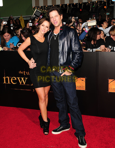 "JENNIFER LOVE HEWITT & JAMIE KENNEDY.Premiere of ""The Twilight Saga: New Moon"" held at The Mann's Village Theatre in Westwood, California, USA. .November 16th, 2009 .full length black dress ankle boots open toe hands on hips  leather jacket couple jeans denim .CAP/RKE/DVS.©DVS/RockinExposures/Capital Pictures."