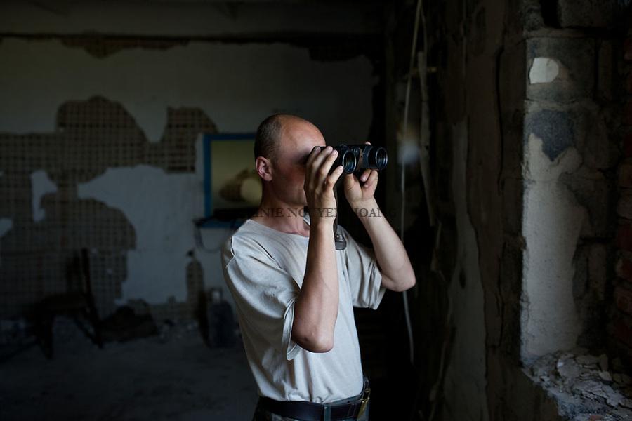 UKRAINE: Frontline of Kamyanka. An Ukrainian soldier  islooking at separatist positions with his binoculars. <br /> <br /> UKRAINE: Frontline de Kamyanka. Un soldat ukrainien regarde vers les positions s&eacute;paratistes avec ses jumelles.