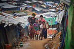 Rohingya refugees walk through the sprawling Kutupalong Refugee Camp near Cox's Bazar, Bangladesh. More than 600,000 Rohingya have fled government-sanctioned violence in Myanmar for safety in Bangladesh.