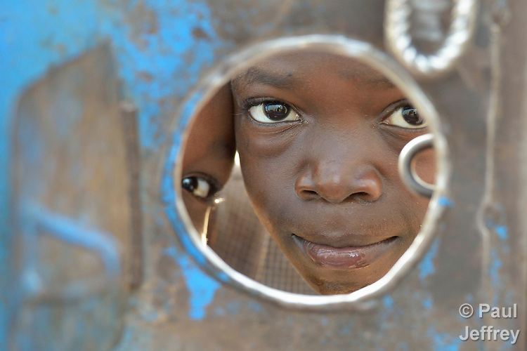 Children look through a hole in a metal gate in a camp for for than 5,000 displaced people in Riimenze, in South Sudan's Gbudwe State, what was formerly Western Equatoria. Families here were displaced at the beginning of 2017, as fighting between government soldiers and rebels escalated.<br /> <br /> Two Catholic groups, Caritas Austria and Solidarity with South Sudan, have played key roles in assuring that the displaced families here have food, shelter and water.