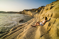 Scala dei Turchi at sunset, a tourist watching the sunset, Realmonte, Agrigento, Sicily, Italy, Europe. This is a photo of a tourist watching the sunset on Scala dei Turchi. Scala dei Turchi is a limestone cliff known as The Turkish Staircase on the Rossello cape at Realmonte near Agrigento in Sicily, Italy. It is without a doubt one of the best places I have ever watched the sunset, as the white limestone cliffs turn a rich orange.