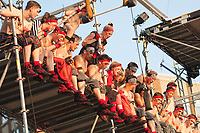 Street performers watch a performance from scaffolding in downtown Montreal, Quebec.