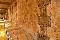 In the wine cellar, rows of new oak barrels with ageing wine and an old and mouldy wall  Chateau Bouscaut Cru Classe Cadaujac  Graves Pessac Leognan  Bordeaux Gironde Aquitaine France