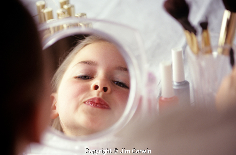 Young girl (8 years old) applying make up to her face looking at herself in mirror smiling and making faces