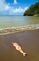Nude sexy woman laying on Caribbean beach.