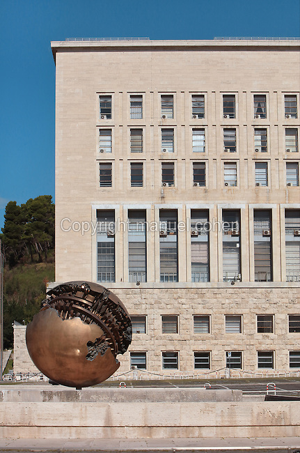 Palazzo della Farnesina, a government building designed 1935 in Fascist style, housing the Ministry of Foreign Affairs, and the bronze sculpture Sfera con Sfera, or Sphere within a Sphere, by Italian sculptor Arnaldo Pomodoro, born 1926, Rome, Italy. Fascist architecture developed in the late 1920s and 1930s, as a modernist style in times of nationalism and totalitarianism under Benito Mussolini. It is characterised by large, square, symmetrical buildings with little or no decoration, often inspired by ancient Rome and designed to convey strength and power. Picture by Manuel Cohen