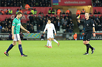 Referee Mike Dean (R) shows a yellow card during the Premier League match between Swansea City and West Bromwich Albion at The Liberty Stadium, Swansea, Wales, UK. Saturday 09 December 2017