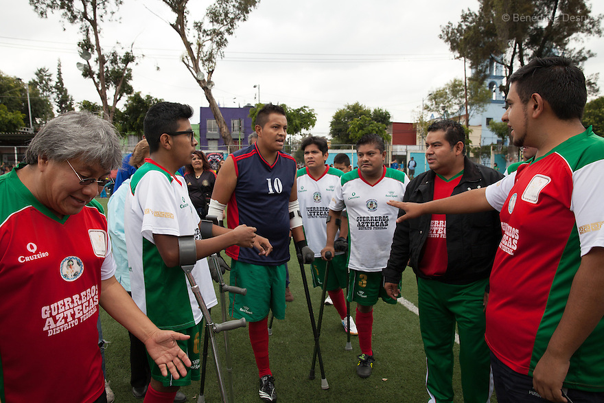 "Players from Guerreros Aztecas discuss tactics before a soccer game against Los Dragones (""the Dragons"") in Mexico City, Mexico on July 5, 2014. Guerreros Aztecas (""Aztec Warriors"") is Mexico City's first amputee football team. Founded in July 2013 by five volunteers, they now have 23 players, seven of them have made the national team's shortlist to represent Mexico at this year's Amputee Soccer World Cup in Sinaloa this December. The team trains twice a week for weekend games with other teams. No prostheses are used, so field players missing a lower extremity can only play using crutches. Those missing an upper extremity play as goalkeepers. The teams play six per side with unlimited substitutions. Each half lasts 25 minutes. The causes of the amputations range from accidents to medical interventions – none of which have stopped the Guerreros Aztecas from continuing to play. The players' age, backgrounds and professions cover the full sweep of Mexican society, and they are united by the will to keep their heads held high in a country where discrimination against the disabled remains widespread. (Photo by Bénédicte Desrus)"