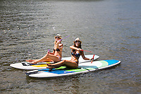 Two young attractive fit women on stand up paddle board, SUP, blowing bubbles in the blue waters of Lake Travis on a hot summer's day in Austin, Texas.