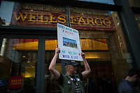 NEW YORK, NY - APRIL 5: An activist holds a placard at the entrance of Wells Fargo bank as activists begin the overnight camp out in front of the bank on April 5, 2017 in Soho, New York City. Activists are looking to drive mayor Bill De Blasio attention to divest founds from banks like Wells Fargo &amp; Company which has caused controversy for their investment in the Dakota Access Pipeline (DAPL)&mdash;a project that will be constructed through land owned by the Standing Rock Indian Reservation and covers land stretching from North Dakota to central Illinois. Photo by VIEWpress/Eduardo MunozAlvarez<br /> <br /> divest