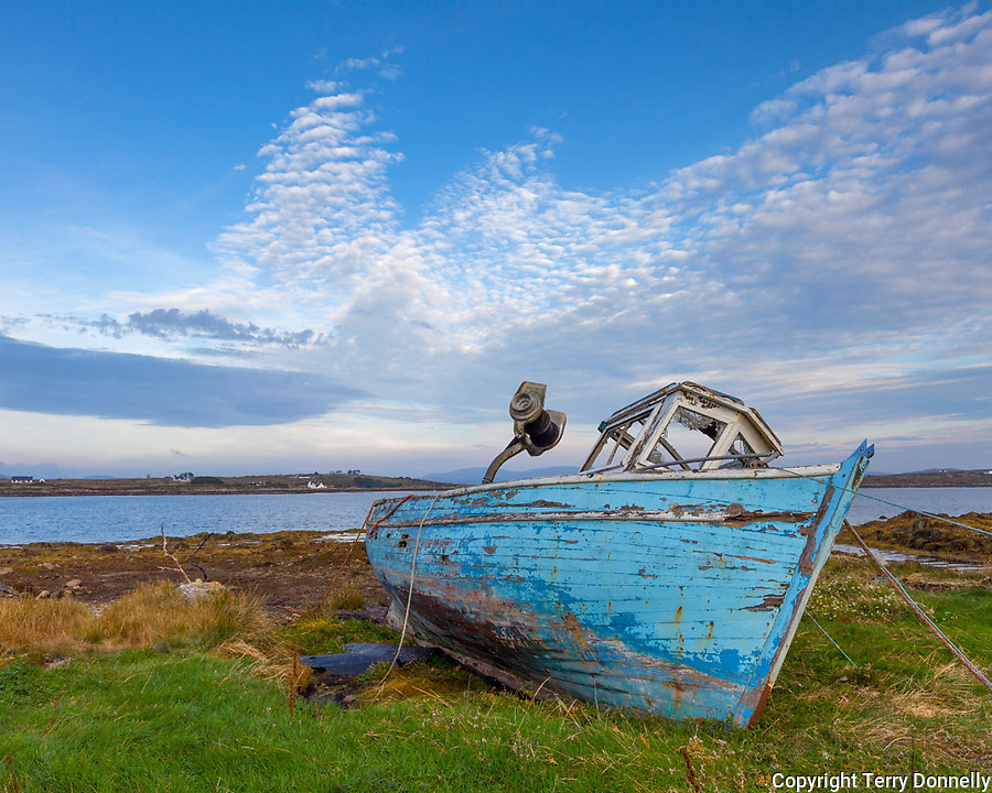 County Galway, Ireland: Evening light on an abandoned wood boat on the shore of Roundstone Harbor