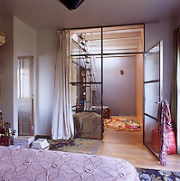 A view from a bedroom with a wooden floor through a glass door to dressing are beyond.