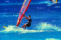 A woman enjoys the ride as she windsurfs at Kahana Beach Park on Maui.