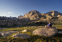 woman hiker, Wind River Range, hiking, Bridger-Teton National Forest, WY, Wyoming, Woman sitting on a large boulder in Titcomb Basin looking at the scenic view of the Wind River Range Mountains in the Bridger-Teton Nat'l Forest in Wyoming.