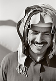 SAUDI ARABIA, smiling Egyptian Bedouin man in traditional clothing, The Empty Quarter, Najran (B&W)