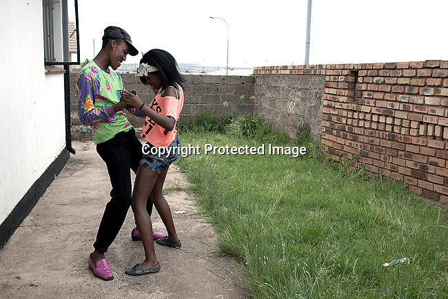 A young couple dance at an Izikhothanes house party in Dobsonville in Soweto, South Africa. The Izikhothane bling kids are the new fears of residents and parents. Young kids who like to drink, buy (and sometimes burn and destroy) fancy brand clothes and shoes in Soweto. They also like to drink and display expensive bottles of alcohol. Many of these kids are desperate to get the latest clothes and the pressure is hard on their parents. Photo by: Per-Anders Pettersson