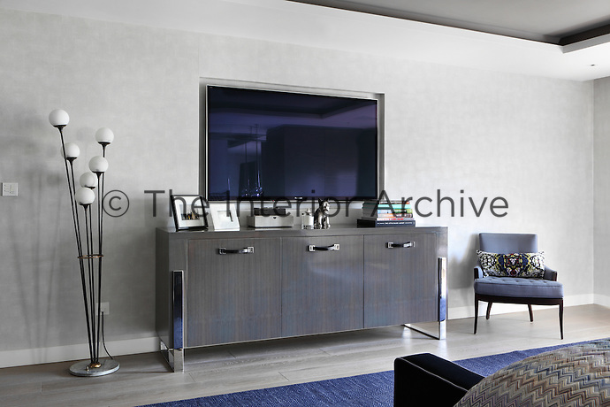 A television hangs in a niche above the sideboard in this bedroom