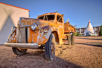 Antique cars and trucks are parked all around the Wig Wam Motel in Holbrook Arizona.