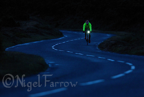 10 JUN 2011 - BRANSGORE, GBR - As the light begins to fail  competitors turn on their bike lights and put on reflective clothing so ready to continue racing through the night during the Triple Enduroman race at the  Enduroman Ultra Triathlon Championships .(PHOTO (C) NIGEL FARROW)