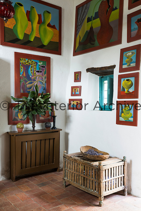 A corner of the sitting room with paintings by South African artist Nicolaas Maritz. Traditional local materials were kept during the restoration of the house, such as the terracotta tiles on the floor.
