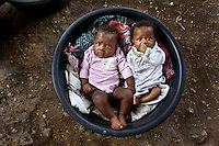 Port-au-Prince, Haiti, 2010. Babies in a bucket, in a tent city after the earthquake. When the quake hit on January 12, 2010, I had been staying in a decadent $10,000 a night villa while photographing the stunning Amanyara on Turks and Caicos Island. One thirty minute flight later I couldn't have been farther from that reality. I met Cecile who offered to have me to sleep outside of her home with all of her family, most having lost everything. Every morning her elderly mother made sure I had a little cup of the thick black Haitian coffee that I came to love, and at night a bowl of water to wash with. They never asked when I was leaving. Three weeks later I boarded a UN evacuation flight to return to New York. Unpacking my small backpack at home I found two pounds of coffee that Cecile had stuffed into it. I drank one and keep the other in my fridge to look at every morning as a reminder of their generosity.  It always seems to be the people who have the least who give the most.
