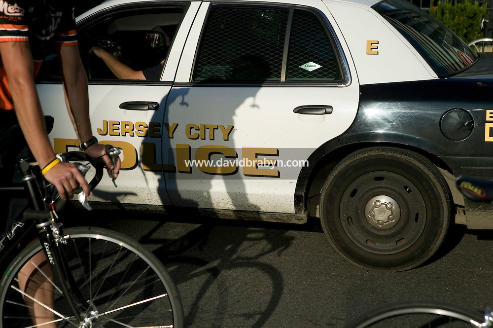 2 July 2005 - Jersey City, NJ, USA - Riders pass police officers dispersing assembled messengers at the end of qualifying events for the 13th annual cycle messenger world championships, Jersey City, USA, July 2nd 2005. More than 700 riders from all over the world took part in the 4-day competition which carries event based on the daily work of a city bike messenger.