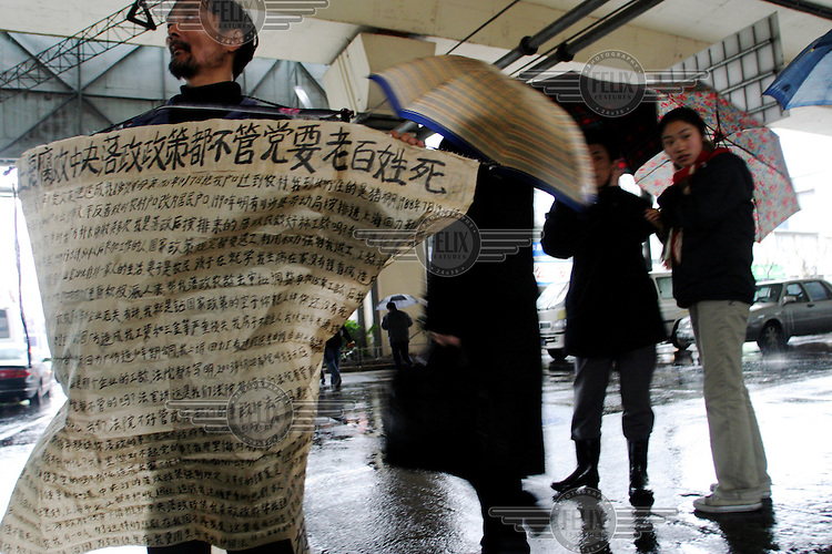 A man wearing a large poster silently protests his forced unemployment and loss of benefits from a Chinese state-owned enterprise (SOE) while standing at a major intersection in downtown Shanghai. The Chinese government had made painful choices in recent years to overhaul its SOEs, laying off tens of millions of workers.