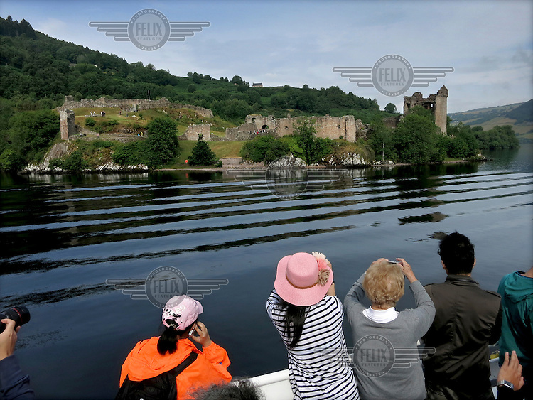 Two Chinese tourists on the Jacobite Ferry that crosses Loch Ness transporting people to Urquhart Castle.