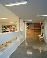A polished concrete entrance hall leads to a double staircase and opens on to a study/office area