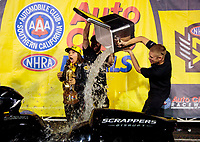 Nov 17, 2019; Pomona, CA, USA; NHRA pro stock motorcycle rider Jianna Salinas is doused with a cooler of ice water by crew members as she celebrates after winning the Auto Club Finals at Auto Club Raceway at Pomona. Mandatory Credit: Mark J. Rebilas-USA TODAY Sports