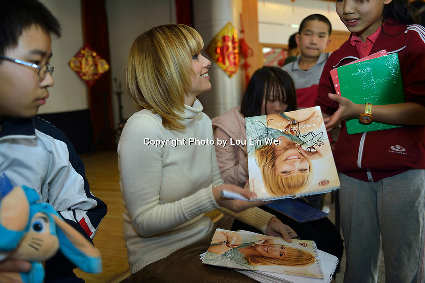 "Swiss singer and TV presenter Francine Jordi gives and signs her calendars while visiting ""SOS Kinderdorf"" in Tianjin, China. 22-Mar-2016"