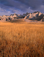SDBD_040 - USA, South Dakota, Badlands National Park, North Unit, Morning light defines storm clouds over autumn-colored grasses and eroded peaks.