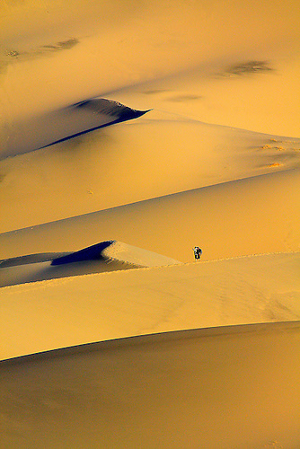 TWO HIKERS ARE DWARFED BY THE 700 FOOT HIGH EUREKA DUNES IN DEATH VALLEY NATIONAL PARK,CALIFORNIA