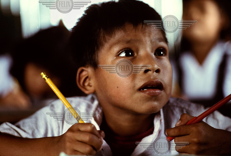 A schoolboy with two pencils concentrates during a lesson at a primary school in a Shipibo community..