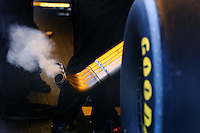 Apr 12, 2015; Las Vegas, NV, USA; Detailed view as smoke comes from the header pipes as NHRA funny car driver Alexis DeJoria warms up her car in the pits during the Summitracing.com Nationals at The Strip at Las Vegas Motor Speedway. Mandatory Credit: Mark J. Rebilas-