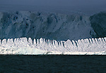 Sunlight highlights a uniquely shaped iceberg, while a larger one looms behind in the shadows.