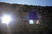 "Machu Picchu, Peru. View up at Inca wall in ""Lost City of Incas"" with windows and sunburst in one window."