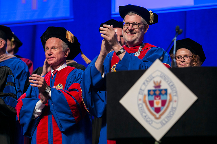 Rick Kash, left, vice chairman of the global consumer information analytics firm Nielsen, and the Rev. Dennis H. Holtschneider, C.M., president of DePaul University, applaud the graduates Sunday, June 11, 2017, during the DePaul University Driehaus College of Business commencement ceremony at the Allstate Arena in Rosemont, IL. (DePaul University/Jamie Moncrief)