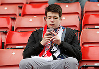 A Swansea fan takes a photo of the ground during the Barclays Premier League match between Stoke City and Swansea City played at Britannia Stadium, Stoke on April 2nd 2016